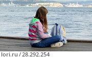 Купить «Girl is reading a book on the embankment near the sea», видеоролик № 28292254, снято 17 октября 2017 г. (c) Tatiana Kravchenko / Фотобанк Лори