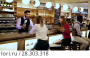Купить «Handsome hispanic barman serving drinks to young people on bar in restaurant», видеоролик № 28303318, снято 27 марта 2018 г. (c) Яков Филимонов / Фотобанк Лори
