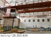 Купить «Overhead cranes with a crane operator cabin and hooks in a multi-span metal frame workshop. Steel landing pad.», фото № 28303434, снято 13 февраля 2018 г. (c) Евгений Ткачёв / Фотобанк Лори