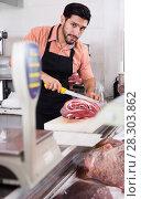 Купить «Positive butcher is cutting meat for clients», фото № 28303862, снято 15 сентября 2017 г. (c) Яков Филимонов / Фотобанк Лори