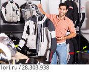 Купить «Man is demonstrating new jacket for motorbike in the store.», фото № 28303938, снято 1 сентября 2017 г. (c) Яков Филимонов / Фотобанк Лори