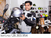 Купить «Male customer in new jacket is choosing modern helmet», фото № 28303954, снято 1 сентября 2017 г. (c) Яков Филимонов / Фотобанк Лори