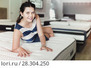 Купить «Customer girl is relaxing lying on new mattress before buying it», фото № 28304250, снято 29 августа 2017 г. (c) Яков Филимонов / Фотобанк Лори