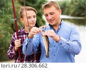 Купить «Man with teenager boy releasing fish from hook», фото № 28306662, снято 10 декабря 2018 г. (c) Яков Филимонов / Фотобанк Лори