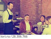 Купить «Male waiter bringing order to visitors», фото № 28306766, снято 22 июля 2018 г. (c) Яков Филимонов / Фотобанк Лори