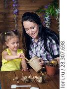 Купить «Mom and child are planting flowers», фото № 28307698, снято 14 апреля 2018 г. (c) Типляшина Евгения / Фотобанк Лори