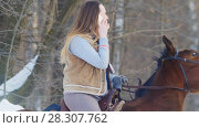 Купить «Beautiful female rider use phone in winter field», фото № 28307762, снято 23 июля 2018 г. (c) Константин Шишкин / Фотобанк Лори