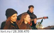 Купить «Cheerful friends singing with the guitar at the sunset outdoors», видеоролик № 28308470, снято 25 апреля 2018 г. (c) Константин Шишкин / Фотобанк Лори