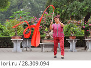 Купить «Old lady practices traditional gymnastics with red ribbon in Jingshan Park in Beijing, China», фото № 28309094, снято 11 декабря 2018 г. (c) BE&W Photo / Фотобанк Лори
