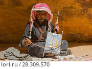 Купить «Old Rebab Bedouin player with his self made instrument singing in the Petra desert, Jordan», фото № 28309570, снято 26 июня 2019 г. (c) BE&W Photo / Фотобанк Лори