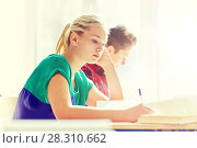 Купить «group of students with books writing school test», фото № 28310662, снято 22 апреля 2016 г. (c) Syda Productions / Фотобанк Лори