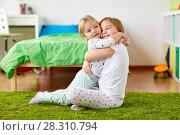 Купить «happy little girls or sisters hugging at home», фото № 28310794, снято 15 октября 2017 г. (c) Syda Productions / Фотобанк Лори