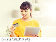 Купить «happy asian woman with tablet pc and credit card», фото № 28310942, снято 9 марта 2016 г. (c) Syda Productions / Фотобанк Лори