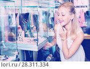 Купить «Portrait of young woman standing next to glass showcases», фото № 28311334, снято 26 марта 2019 г. (c) Яков Филимонов / Фотобанк Лори
