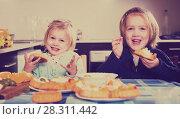 Купить «Kids eating tasty pastry indoors», фото № 28311442, снято 14 декабря 2018 г. (c) Яков Филимонов / Фотобанк Лори