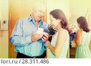 Купить «Senior man came to mature woman with gift», фото № 28311486, снято 20 апреля 2018 г. (c) Яков Филимонов / Фотобанк Лори