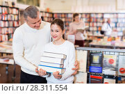 Купить «Portrait of tweenage girl with father standing in library with pile of books in hands», фото № 28311554, снято 22 февраля 2018 г. (c) Яков Филимонов / Фотобанк Лори