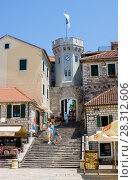 Herceg Novi, Montenegro - July 8, 2015: Old town gate with the small clocktower surrounded by old houses. Редакционное фото, фотограф Papoyan Irina / Фотобанк Лори
