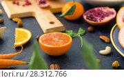 Купить «close up of fruits, nuts and vegetables on table», видеоролик № 28312766, снято 8 апреля 2018 г. (c) Syda Productions / Фотобанк Лори