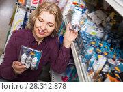 Купить «Adult woman buys light bulbs at the store», фото № 28312878, снято 19 февраля 2020 г. (c) Яков Филимонов / Фотобанк Лори