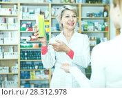 Купить «Mature female seller suggesting care products to young customer», фото № 28312978, снято 15 марта 2017 г. (c) Яков Филимонов / Фотобанк Лори