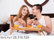 Купить «Pleasant smiling couple reading news from smartphone», фото № 28316526, снято 3 августа 2020 г. (c) Яков Филимонов / Фотобанк Лори