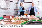 Купить «Mature seller and assistant offering frozen seafood», фото № 28316538, снято 5 июля 2020 г. (c) Яков Филимонов / Фотобанк Лори