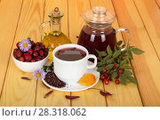Pitcher of broth hips, dried fruits in bowl, branch with berries and leaves, on wooden table. Стоковое фото, фотограф Сергей Молодиков / Фотобанк Лори