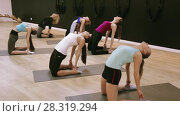 Smiling young women training yoga positions in modern yoga studio. Стоковое видео, видеограф Яков Филимонов / Фотобанк Лори