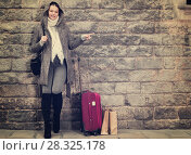 Купить «cheerful female with baggage near wall», фото № 28325178, снято 11 ноября 2017 г. (c) Яков Филимонов / Фотобанк Лори