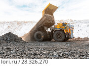 Купить «Large quarry dump truck. Loading the rock in dumper. Loading coal into body truck. Production useful minerals. Mining truck mining machinery, to transport coal from open-pit as the Coal Production.», фото № 28326270, снято 15 февраля 2018 г. (c) Сергей Тимофеев / Фотобанк Лори