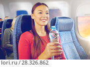 Купить «happy young woman with water bottle in plane», фото № 28326862, снято 21 октября 2015 г. (c) Syda Productions / Фотобанк Лори
