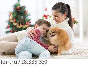 Купить «Family mother and her son play with dog at christmas tree», фото № 28335330, снято 3 мая 2017 г. (c) Оксана Кузьмина / Фотобанк Лори