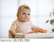 Купить «baby girl eating messy spaghetti», фото № 28335358, снято 30 марта 2020 г. (c) Оксана Кузьмина / Фотобанк Лори