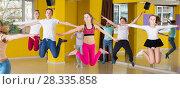 Купить «Children with teacher jumping in dance hall», фото № 28335858, снято 3 марта 2018 г. (c) Яков Филимонов / Фотобанк Лори