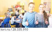 Купить «Two satisfied children standing in schoolroom on background with pupils studying», фото № 28335910, снято 28 января 2018 г. (c) Яков Филимонов / Фотобанк Лори
