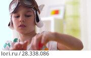 Купить «boy in pilot hat playing with airplane toy at home», видеоролик № 28338086, снято 20 апреля 2018 г. (c) Syda Productions / Фотобанк Лори