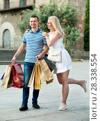 Купить «Young man and woman holding shopping paper bags», фото № 28338554, снято 23 января 2019 г. (c) Яков Филимонов / Фотобанк Лори