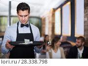 Купить «disgruntled waiter holding serving tray with tips», фото № 28338798, снято 11 декабря 2017 г. (c) Яков Филимонов / Фотобанк Лори