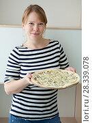 Купить «Женщина в полосатой футболке стоит с вкусной пиццей в руках», фото № 28339078, снято 15 апреля 2018 г. (c) Кекяляйнен Андрей / Фотобанк Лори