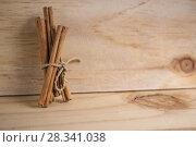 Купить «Палочки корицы на деревянном фоне», фото № 28341038, снято 26 апреля 2018 г. (c) NataMint / Фотобанк Лори
