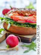 Fresh bagel with arugula, radish and smoked trout. Стоковое фото, фотограф Марина Сапрунова / Фотобанк Лори