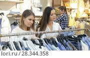 Купить «Portrait of smiling women choosing clothes in the modern shop», видеоролик № 28344358, снято 27 марта 2018 г. (c) Яков Филимонов / Фотобанк Лори