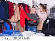Купить «Cheerful teen girl looking for clothing with mum», фото № 28347646, снято 21 марта 2018 г. (c) Яков Филимонов / Фотобанк Лори
