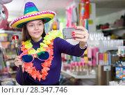 Купить «Girl taking selfie in store of festival accessories», фото № 28347746, снято 15 марта 2018 г. (c) Яков Филимонов / Фотобанк Лори