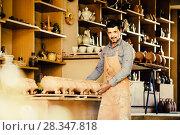 Купить «merry man potter holding ceramic vessels», фото № 28347818, снято 20 октября 2018 г. (c) Яков Филимонов / Фотобанк Лори