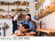 Купить «Workers in ceramics studio with pottery wheel», фото № 28347850, снято 19 августа 2018 г. (c) Яков Филимонов / Фотобанк Лори