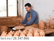 Купить «Positive male working with clay on pottery wheel», фото № 28347866, снято 19 августа 2018 г. (c) Яков Филимонов / Фотобанк Лори