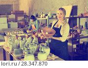 Купить «Portrait of glad woman pottery worker with ceramic crockery», фото № 28347870, снято 19 августа 2018 г. (c) Яков Филимонов / Фотобанк Лори