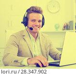 Купить «Young man working in call centre», фото № 28347902, снято 14 декабря 2019 г. (c) Яков Филимонов / Фотобанк Лори